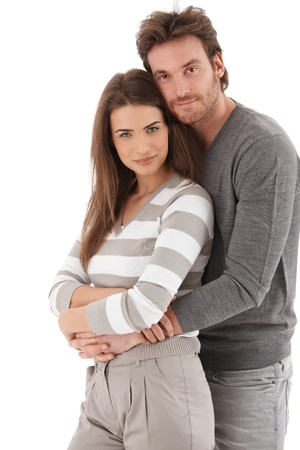 Portrait of attractive young loving couple smiling at camera, embracing.