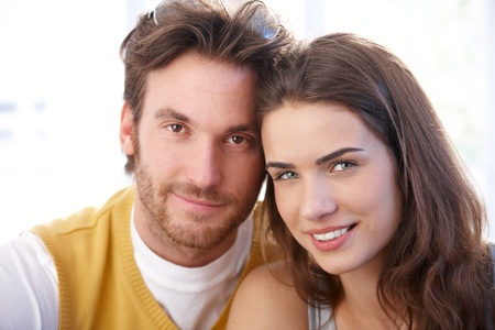 Closeup portrait of attractive young loving couple, smiling, looking at camera.