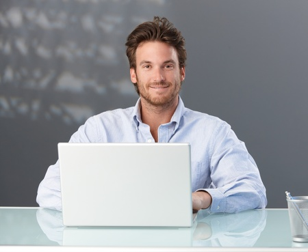 Casual businessman sitting in office with laptop computer, smiling at camera.