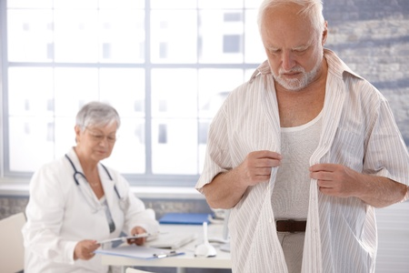 Mature male patient undressing at doctor's room.