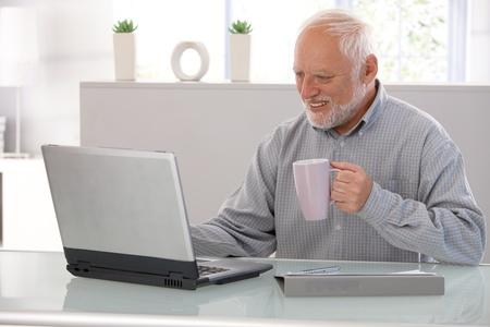 Elderly man working on laptop, smiling, looking at screen, drinking tea.