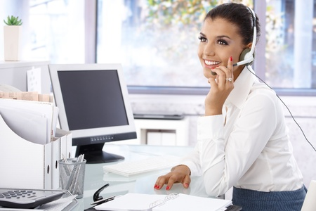 Attractive young dispatcher working in bright office, sitting at desk, smiling.