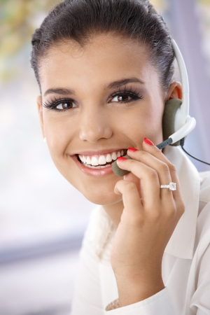 Closeup portrait of beautiful young dispatcher, smiling, looking at camera.