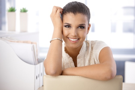 Portrait of beautiful young smiling girl in office.