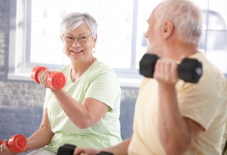 Foto de Vital senior couple exercising in the gym. - Imagen libre de derechos