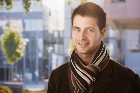 Outdoors portrait of handsome guy standing outside of office building, wearing scarf.