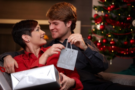 Happy young man giving christmas present to his girlfriend, smiling.