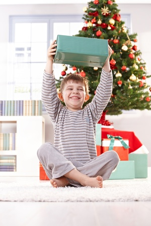 Small boy laughing, sitting on floor in morning, holding up christmas present happily.
