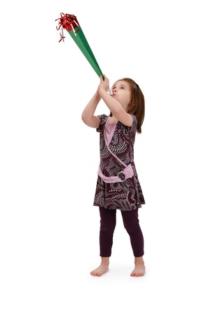 Little girl in cute pretty dress blowing party horn, celebrating.