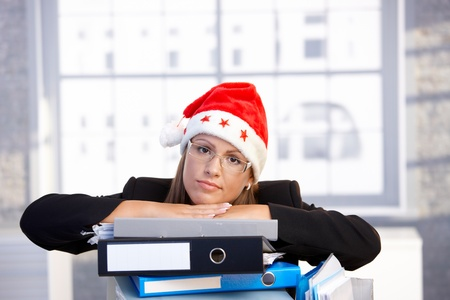 young woman in santa hat sitting in office leaning on folders, having trouble.ᅵ