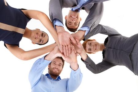 Smiling businesspeople putting hands together, view from below.
