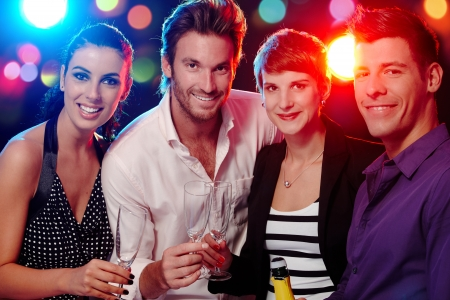 Photo pour Happy companionship drinking, smiling in discotheque. - image libre de droit