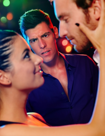 Desperate jealous man looking at flirting couple in discotheque.