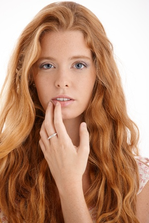 Pretty redhead portrait, closeup face and hand, touching lips, looking at camera, beautiful long red curly hair.