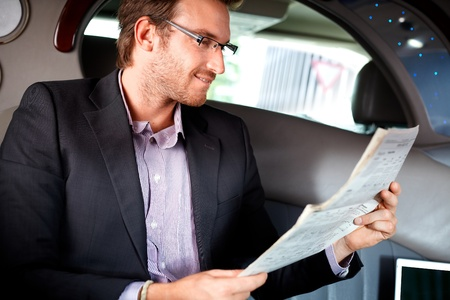 Elegant young man reading newspaper in luxury car.