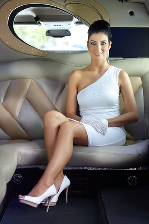 Elegant luxury woman sitting in limousine, smiling.