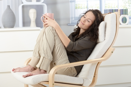 Woman relaxing with closed eyes and cup of tea in armchair at home, daydreaming.