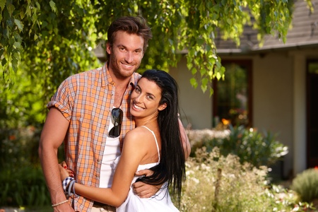 Attractive loving couple smiling happily at summertime in the garden.