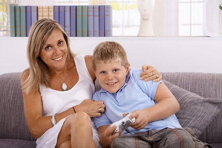Photo pour Little boy and mother playing video game, smiling, having fun. - image libre de droit