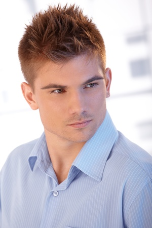 Closeup portrait if handsome young man with cool hairdo posing.