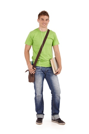Photo pour Smiling university student boy standing with books and bag, listening to music via earphones, white background. - image libre de droit