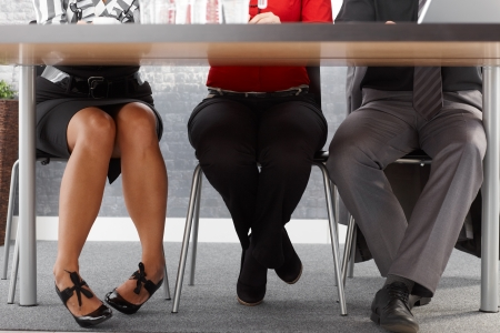 Legs of businesspeople at meeting, sitting together at meeting table in office.