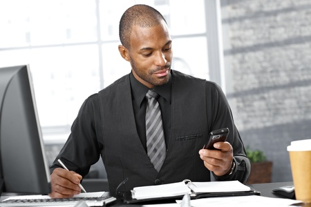 Portrait of smart businessman busy working at desk, using mobile phone, taking notes, concentrating .