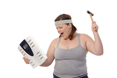 Angry fat woman punching scale by hammer, shouting.