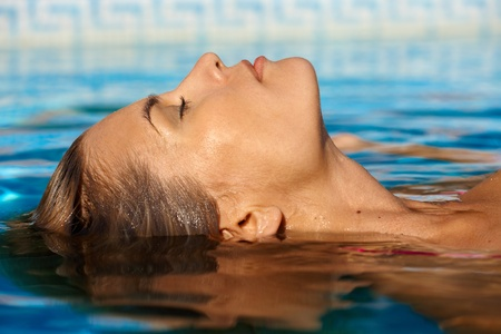 Photo for Young woman enjoying water and sun in outdoor swimming pool. - Royalty Free Image