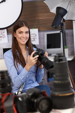 Beautiful photographer girl sitting in studio with camera handheld, surrounded by camera lens and equipment, selective focus.
