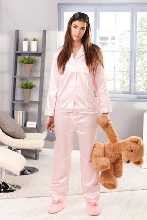 Portrait of attractive sleepy woman standing in pyjama with teddy bear and coffee mug handheld in living room.