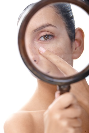 Photo pour Young woman examining her skin by magnifying glass, looking for blackheads. - image libre de droit