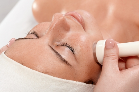 Photo for Closeup portrait of young woman receiving facial beauty treatment, laying eyes closed. - Royalty Free Image