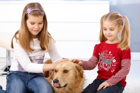 Little girls stroking golden retriever, smiling.
