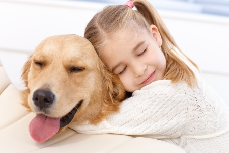 Lovely little girl hugging pet dog with passion, eyes closed.