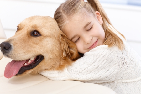 Foto de Cute little girl hugging golden retriever with love eyes closed, smiling. - Imagen libre de derechos