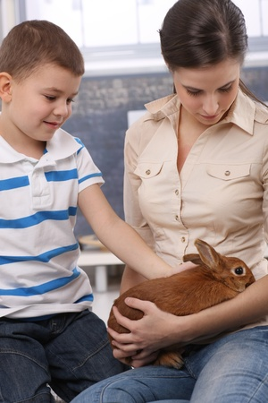 Cute kid and mum stroking pet bunny at home.