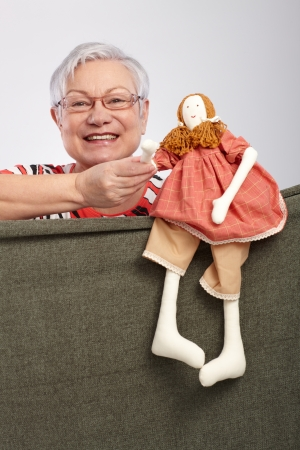 Elderly lady playing puppet show, holding puppet doll in hand, smiling   65533;