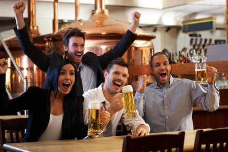 Photo pour Happy friends in pub watching sport in TV together drinking beer cheering for team and celebrating. - image libre de droit