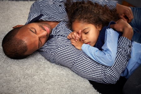 Ethnic father and beautiful little daughter sleeping on floor at home