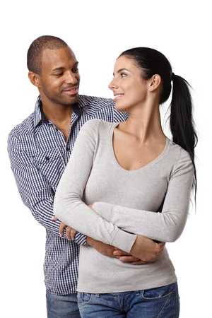 Diverse loving couple holding hands, embracing, smiling at each other.