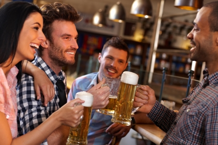 Photo pour Happy young friends drinking beer, having fun in pub, smiling. - image libre de droit