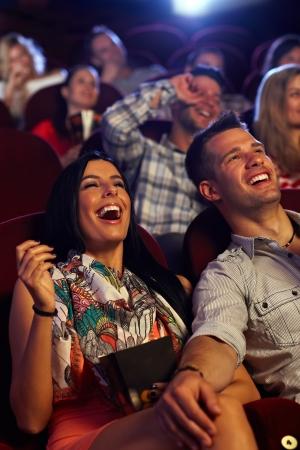Foto de Happy couple watching comedy in movie theater, laughing. - Imagen libre de derechos