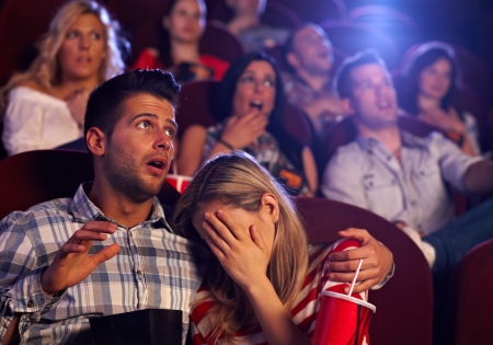 Young couple watching horror movie in cinema, girl turning her head away with fear.