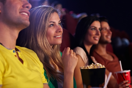 Young woman sitting in cinema, watching movie, smiling.