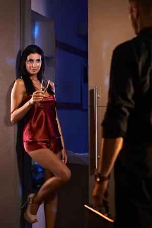 Sexy woman standing in bedroom door in red silk pyjamas, greeting man arriving from work.