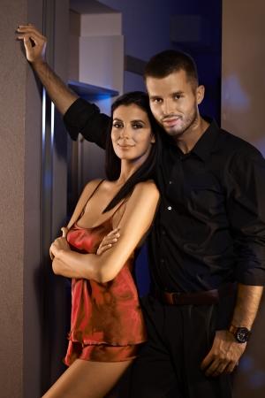 Happy couple standing at door, woman in sexy pyjamas, both smiling.