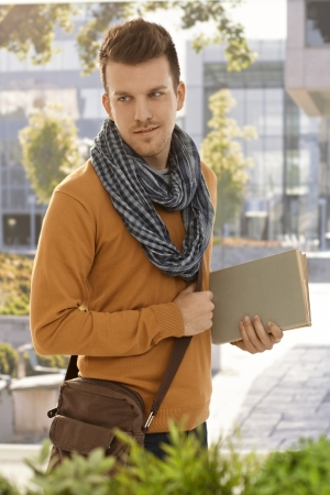 Portrait of male student holding books outdoors.