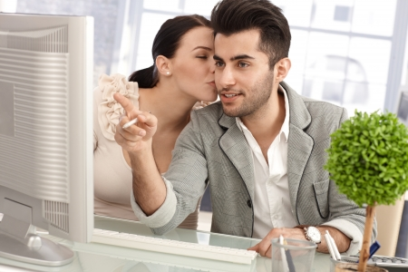 Young colleagues flirting in workplace, woman kissing man while working together.