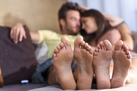 Young loving couple lying on sofa at home, relaxing in the afternoon  Focus on feet